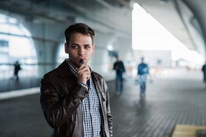 lifestyle portrait of a man vaping near the airport before registration with custom vape mod device.